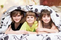 Roliga skinn för små systrar under en filt Royaltyfri Bild