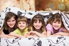 Roliga skinn för små systrar under en filt Arkivbild