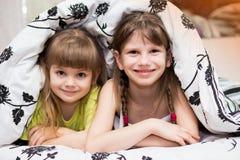 Roliga skinn för små systrar under filten Arkivbilder