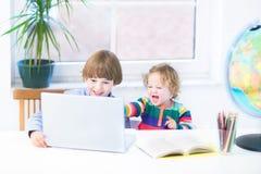 Roliga skratta ungar som spelar samman med en bärbar dator Arkivbilder