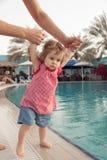 Roliga små behandla som ett barn flickan nära simbassäng Fadern rymmer spädbarnet vid händer på pölbakgrund Sommarsemester med royaltyfri fotografi