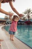 Roliga små behandla som ett barn flickan nära simbassäng Fadern rymmer spädbarnet vid händer på pölbakgrund Sommarsemester med arkivbild