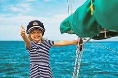 Roliga små behandla som ett barn kaptenen ombord av seglingyachten royaltyfri bild