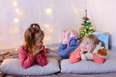 Roliga små flickor skrattar och talar och att posera att ligga på golv och på royaltyfri foto
