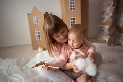 Roliga små systrar (sibling) som spelar i hus för en papp, l Arkivfoton