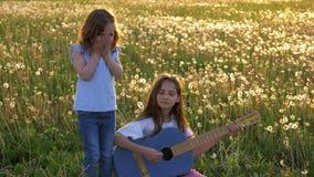Roliga systrar som sjunger och spelar den akustiska jeansgitarren på ett maskrosfält små flickor som har rolig fritid på utomhus arkivfilmer