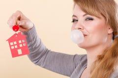 Roliga tangenter för kvinnahållhus äter tuggummi Arkivfoto