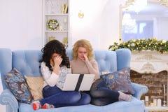 Roliga trevliga vänner spenderar angenäm afton på datoren som sitter nolla Royaltyfria Bilder