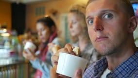 Roliga unga vänner för blandat lopp som äter glass och omkring bedrar i kafé thailand Slowmotion HD lager videofilmer