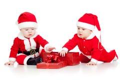 Roliga ungar i Santa Claus kläder med gåvaasken Fotografering för Bildbyråer