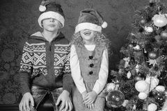 Roliga ungar på jul semestrar nära dekorerat julträd Arkivbilder