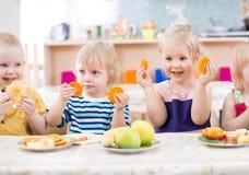 Roliga ungar som äter frukter i dinning rum för dagis Royaltyfri Fotografi