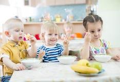 Roliga ungar som äter i dagis arkivbilder