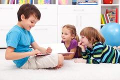 roliga ungar som läser berättelse Fotografering för Bildbyråer