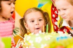Roliga ungar som slår stearinljus på caken Royaltyfri Bild