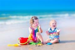 Roliga ungar som spelar på stranden Royaltyfri Foto