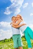 Roliga ungar som tillsammans kramar på en äng Royaltyfri Foto
