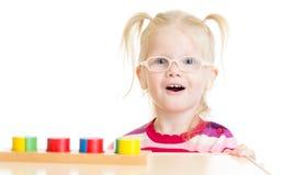 Roligt barn i eyeglases som spelar den logiska leken Royaltyfri Foto
