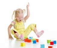 Roligt barn i eyeglases som spelar färgrik byggnad Fotografering för Bildbyråer