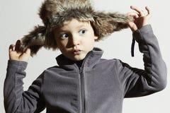 Roligt barn i pälshatt Ungar danar tillfällig vinterstil pojke little Barnsinnesrörelse Royaltyfri Fotografi