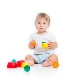 Roligt barn som leker med toys som sitter på golv Arkivfoto