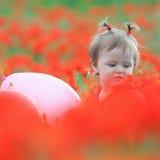 Roligt barn som rymmer en ballong utomhus- på vallmofältet Royaltyfri Bild
