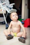 Roligt behandla som ett barn att sitta för pojke som är naket på golvet Royaltyfri Bild