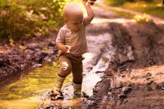 Roligt behandla som ett barn den pojken i gummistöveler som har gyckel i en skogpöl Fotografering för Bildbyråer