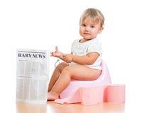 Roligt behandla som ett barn flickaavläsningstidningen på chamberpot Royaltyfri Bild