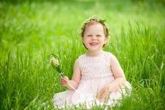 Roligt behandla som ett barn flickan i krans av att le för blommor Arkivbild