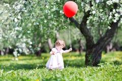 Roligt behandla som ett barn flickan i trädgård för äppleträd med röd ballon Royaltyfria Foton