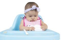 Roligt behandla som ett barn flickan som äter mat på stol Fotografering för Bildbyråer