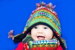 Roligt behandla som ett barn i en färgrik stucken hatt på blå bakgrund Royaltyfria Foton