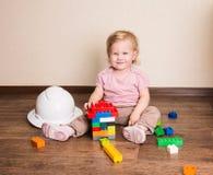 Roligt behandla som ett barn lilla barnet som bygger ett hus av det plast- konstruktörkvarteret Arkivfoto