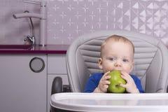 Roligt behandla som ett barn pojken med det stora gröna äpplet i köket arkivbilder