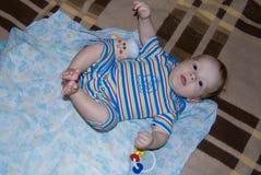 Roligt behandla som ett barn pojken på en säng som ligger lyckligt i blå randig sparkbyxor - Arkivbild