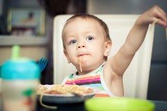Roligt behandla som ett barn pojken som äter spagetti Arkivfoto