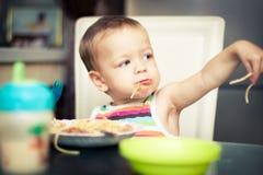 Roligt behandla som ett barn pojken som äter spagetti Royaltyfria Bilder