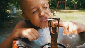 Roligt dricksvatten för lycklig barnpojke från en dricka springbrunn på lekplatsen i ultrarapid arkivfilmer