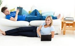 roligt glatt för par ha vardagsrum tillsammans royaltyfri bild
