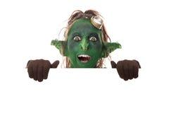 Roligt grönt elakt troll som ser över copyspace Arkivbilder