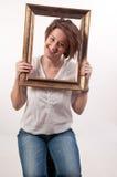 Roligt härligt kvinnainnehav runt om hennes framsida en ram Royaltyfria Foton