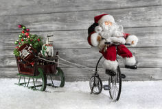 Roligt julhälsningkort med jultomten på en cykel som drar en sli fotografering för bildbyråer