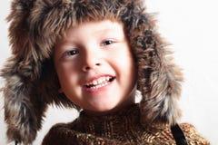 Roligt le barn i en pälshatt. modeunge. vinterstil. pys. barn Fotografering för Bildbyråer