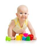 Roligt lite barn som leker med toys över vit Arkivbild