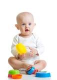 Roligt lite barn som leker med toys över vit Royaltyfri Bild