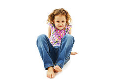 Roligt liten flickasammanträde på däcka i jeans Royaltyfri Foto
