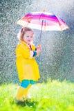 Roligt litet barn med paraplyet som spelar i regnet arkivfoto