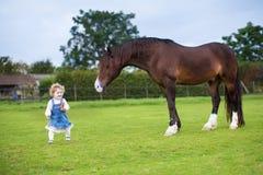 Roligt lockigt behandla som ett barn flickan med den nästa hästen för moroten Royaltyfria Foton