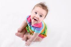 Roligt lyckligt behandla som ett barn i en färgrik randig klänning Royaltyfri Foto